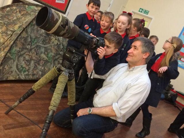 One boy peers through the viewfinder of a camera with a long telephoto lens while other pupils look on