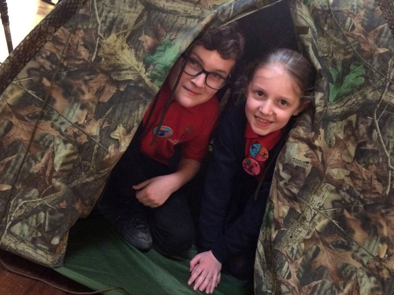 A smiling boy and girl pose in the tent