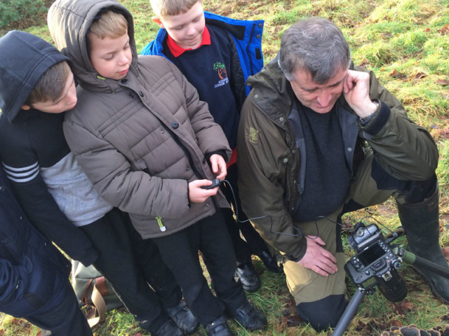 Laurie Campbells helps a pupil set up a photo
